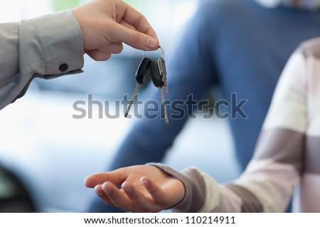 Car dealer giving keys to a customer in a car shop