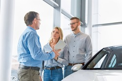 Car dealer helping young couple choose a new car by showing the advantages of the vehicle to the customers