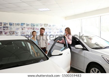 Car dealership sales person at work concept. Portrait of young sales representative wearing formal wear suit, showing vehicles at automobile exhibit center. Close up, copy space, background. #1500359483
