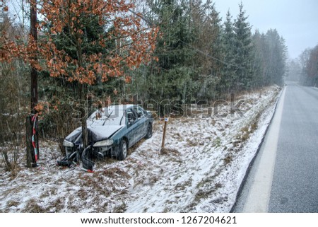 Car destroyed during the traffic accident. It was caused by the bad weather conditions in winter, because of the black ice or snow. The car is abandoned and stands by the road in the snowfall.