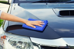 Car detailing and cleaning by hand and microfiber towel. Polishing the car exterior with car shine products or wax result in shine surface. Car care service concept with washing, cleaning, waxing etc.
