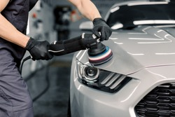 Car detailing and polishing concept. Hands of professional car service male worker, with orbital polisher, polishing white luxury car hood in auto repair shop