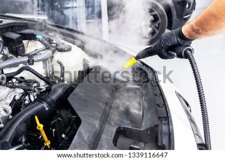 Car detailing. Car washing cleaning engine. Cleaning car using hot steam. Hot Steam engine washing. Soft lighting. Car wash man worker cleaning vehicle. #1339116647