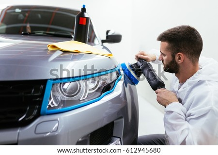 Car detailing - Hands with orbital polisher in auto repair shop. Front lights protected with isolation blue tape. Selective focus. #612945680