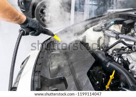 Car detailing maintenance. Cleaning engine with hot steam. High pressure washing. Washing at the station. Car washing concept. Car detailing. Cleaning car engine concept #1199114047