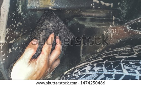 Car Detailing Process. Cleaning Tire with shampoo and Black Sponge background.
