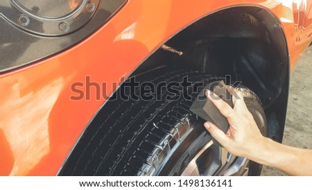 Car Detailing process. Spray and Wax black tire alloy wheel with sponge background. #1498136141