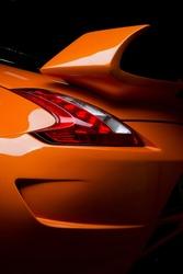 Car detailing series: Clean of rear orange sports car in the dark