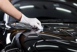 Car detailing series : Closeup of hand coating black car bonnet