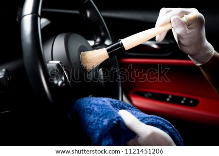 Car detailing series, Man use brush cleaning on hand wheel.