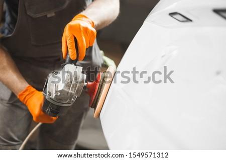 Car detailing series : man waxing auto in auto repair shop. #1549571312