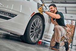 Car detailing series. Worker cleaning white car. Selective focus. Low angle view.