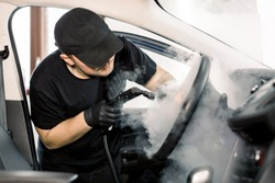 Car detailing, steam cleaning concept. Handsome man in black t-shirt and cap, worker of car wash center, cleaning car interior with hot steam cleaner. Car detailing concept