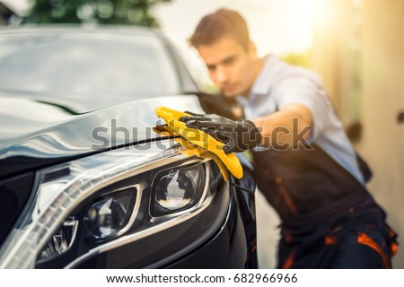 Car detailing - the man holds the microfiber in hand and polishes the car. Selective focus. #682966966