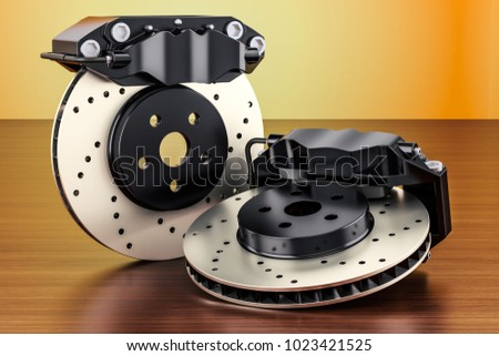 Car discs brake and calipers on the wooden table. 3D rendering
