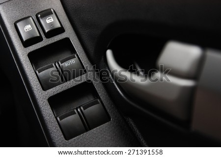Car door interior arm rest with window control panel, door lock button, and mirror control. #271391558