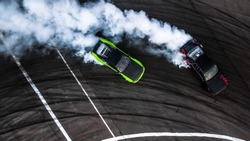 Car drift battle, Two car drifting battle on race track with smoke, Aerial view, Car drifting, Race drift car with lots of smoke from burning tires on speed track.