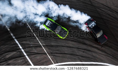 Car drift battle, Two car drifting battle on race track with smoke, Aerial view, Car drifting, Race drift car with lots of smoke from burning tires on speed track. Stock photo ©