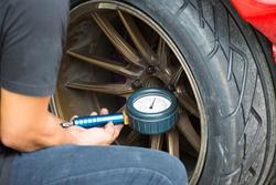 Car drifting, man hand check tire pressure / inflate car tire