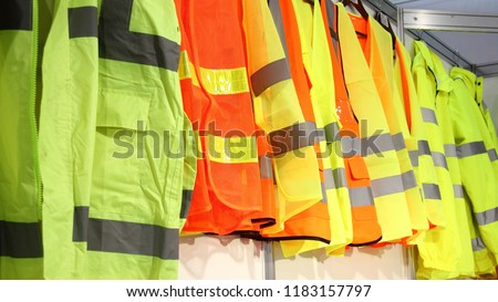 Car driver and road workers special clothing - new bright jackets with reflective stripes in showroom #1183157797