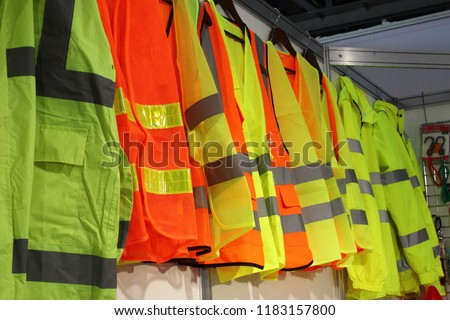 Car driver and road workers special clothing - new bright jackets with reflective stripes in showroom #1183157800
