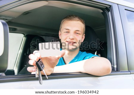 Car driver. Caucasian teen boy showing an empty white card for your message, new car key and car. Happy smiling young man behind the wheel. Travel and rental concept. Copy space, close up.