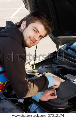 Car driver examining the car's engine on a parking #37312174