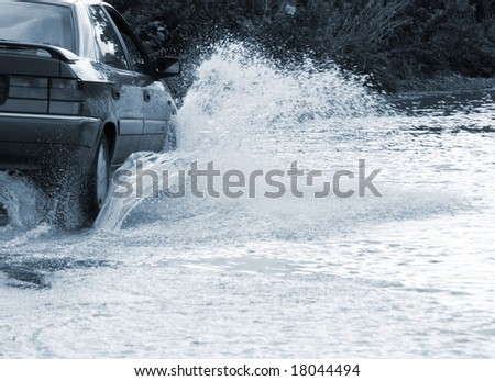 Car drives through flooded road in Yorkshire - stock photo