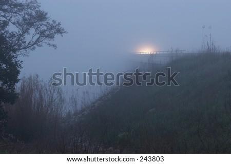 Car driving along a foggy bridge