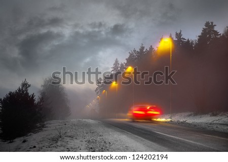 Car driving along rural road on winter evening