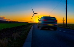 Car driving down country road towards wind turbines in a field in the UK at sunset or sunrise on  a clear winter day