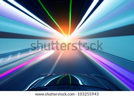 Car driving fast down interior tunnel.