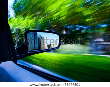 car driving fast escape the city into forest. - stock photo