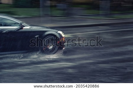 Car driving fast through puddle at heavy rain, dangers of aquaplaning, water splashing over the car. Car driving at heavy rain in evening. Dangerous driving conditions. MOTION BLUR