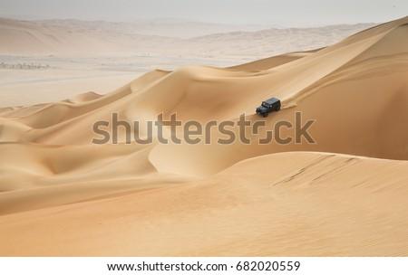 car driving in Rub al Khali Desert at the Empty Quarter, in Abu Dhabi, United Arab Emirates #682020559
