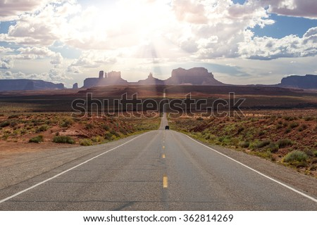 Car driving on American desert highway. Road to Monument Valley State Park in Arizona and Utah