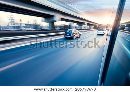 Car driving on freeway at sunset, motion blur #205799698