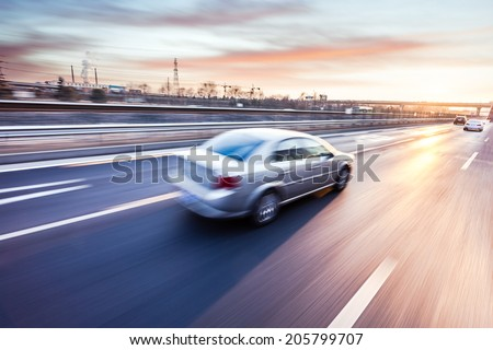 Car driving on freeway at sunset, motion blur #205799707