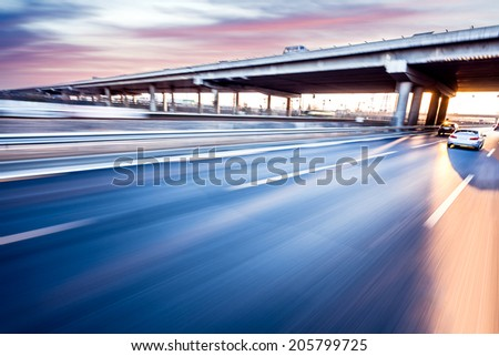 Car driving on freeway at sunset motion blur
