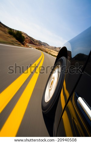 car driving on mountain road - low angle with natural motion blur, focus on wheel