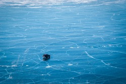 Car driving on natural breaking ice in frozen water at Lake Baikal, Siberia, Russia.