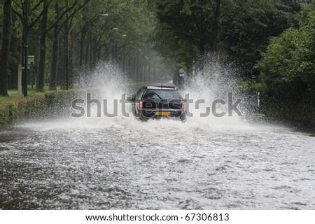 Car driving through a flooded street (Baarn, the Netherlands)