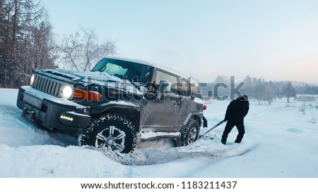 Car driving through a winter storm with snow on a forested road. Black SUV  sticks in deep snow slips. #1183211437
