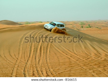 Car driving through desert sand