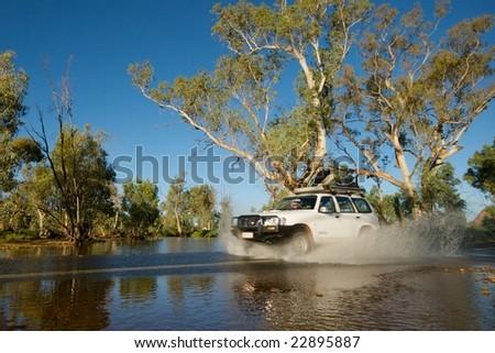 Car driving through river making splash