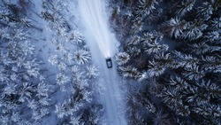 Car driving through the winter snowy forest on country road at night. Top down view.