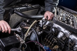 Car engine repair. Diesel engine services. Hands with a mechanic with a wrench repair Mercedes parts.