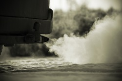 Car exhaust pipe, which comes out strongly of smoke in Finland. Focal point is the center of the photo. Background out of focus. Image includes a effect.