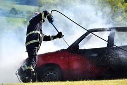 Car fire. A firefighter extinguishes a car fire with foam. Red car on fire, white smoke and firefighter. Accident in the meadow.