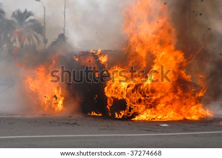 Car fire and firefighter trying to extinguish the flames - stock photo